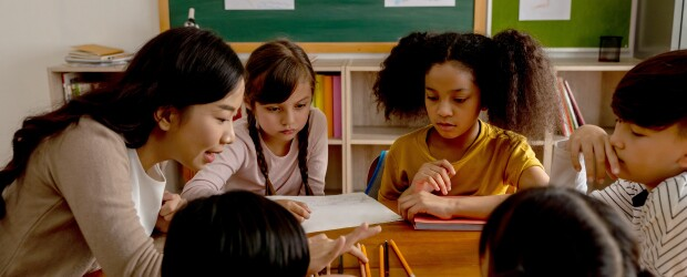 woman-teaching-five-kids-green-chalkboard-in-background