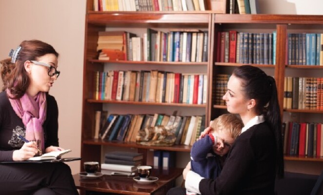 mother holding baby talking to counselor in office