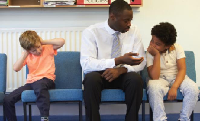 African man sitting with two children in school hallway