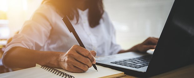 woman-writing-in-notebook-on-laptop-backlit