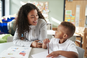 Female-infant-school-teacher-working-one-on-one-with-a-young-schoolboy-sitting-at-a-table-smiling-at-each-other-close-up