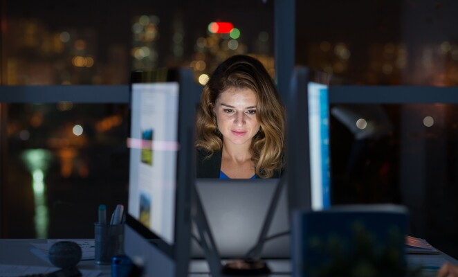 Woman works at night at her office on computer