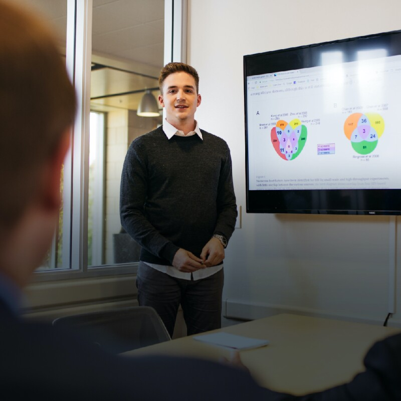 Man stands in conference room in front of a tv screen with graphs