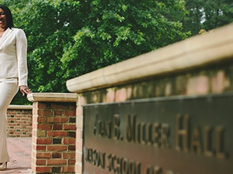 William & Mary MBA student standing in front of Alan B Miller Hall at William & MAry's campus