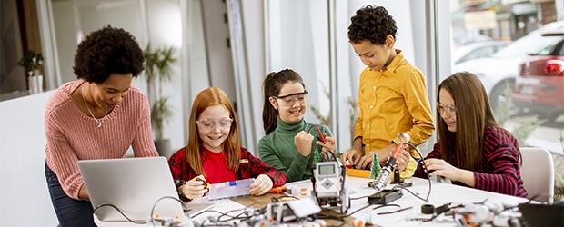 teacher working with four kids stem