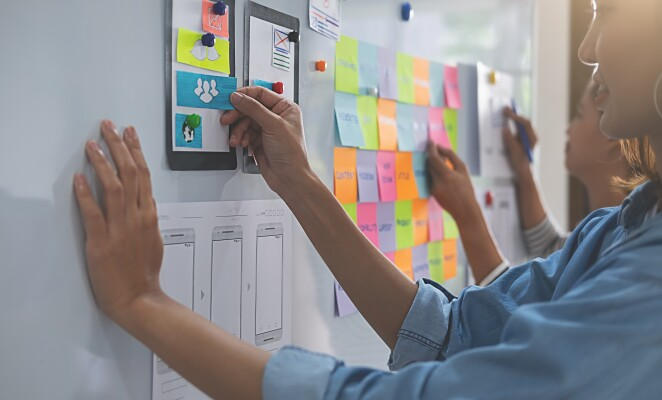 Workers stand at a white board with mobile prototypes and sticky notes