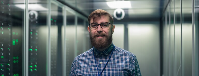 Male professional stands in server room