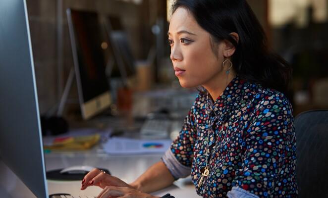 Woman in polka dot denim shirt works at a desktop computer