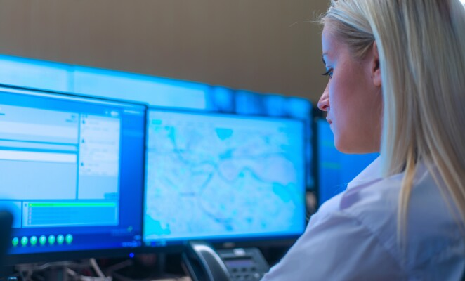 Professional observes data and security footage on screen