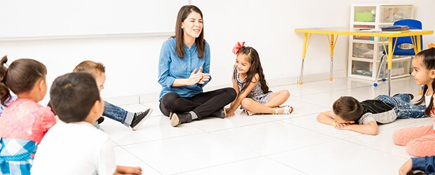 teacher and students sitting on floor in circle