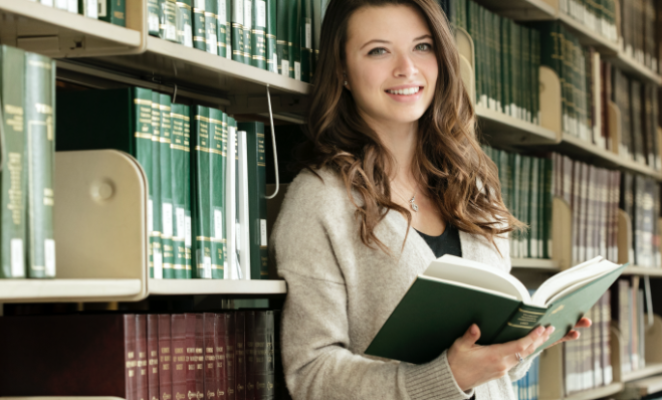 a person reads a bound journal in law library bookstacks