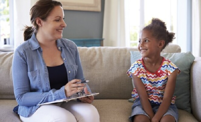 woman sitting on couch with young child smiling