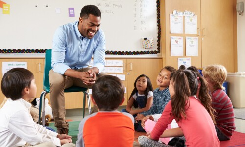 Teacher sitting in circle with preschool students