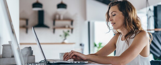 woman in white tank top seated at kitchen table completing coursework on laptop