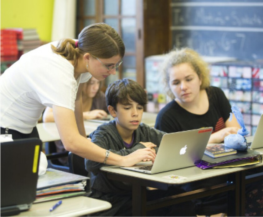 Female educator works with student on laptop