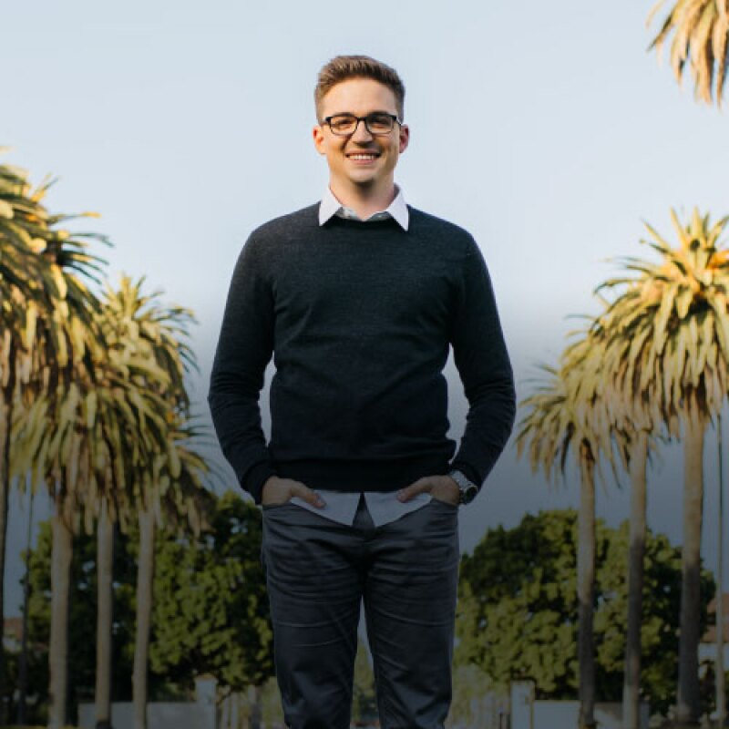 Man in black sweater and glasses stands under palm trees