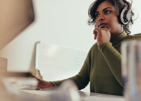 Woman wearing wearing headphones contemplates project at her desk