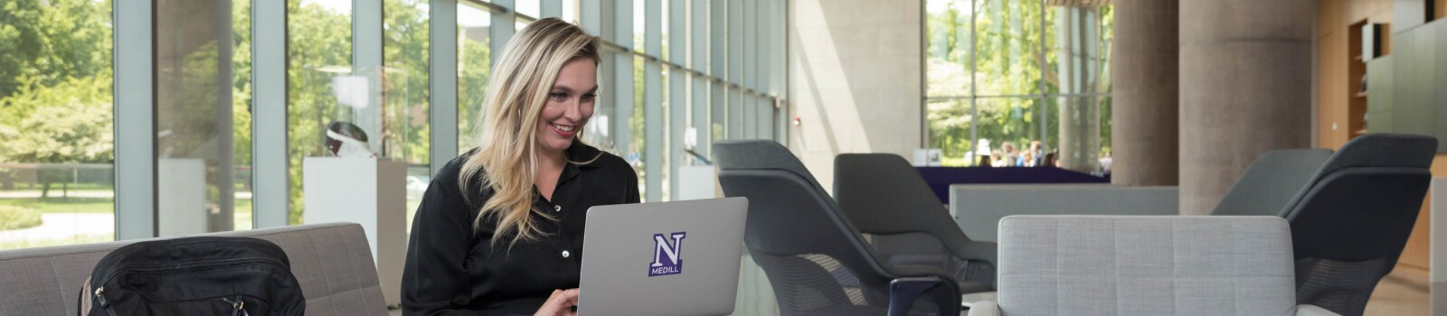 IMC graduate on laptop in the lobby of the Evanston campus