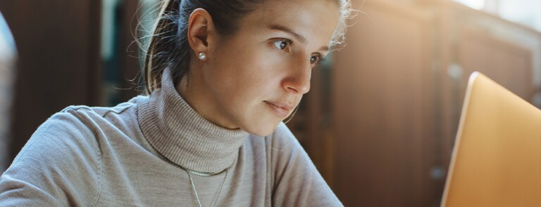 woman in beige turtle neck sweater smiling
