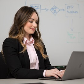 Woman In Suit Working On Laptop