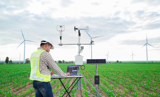 Engineer using tablet computer to collect data with meteorological instrument to measure the wind speed, temperature and humidity and solar cell system on corn field background, Smart agriculture technology concept