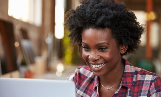 Woman in plaid shirt smiles at laptop