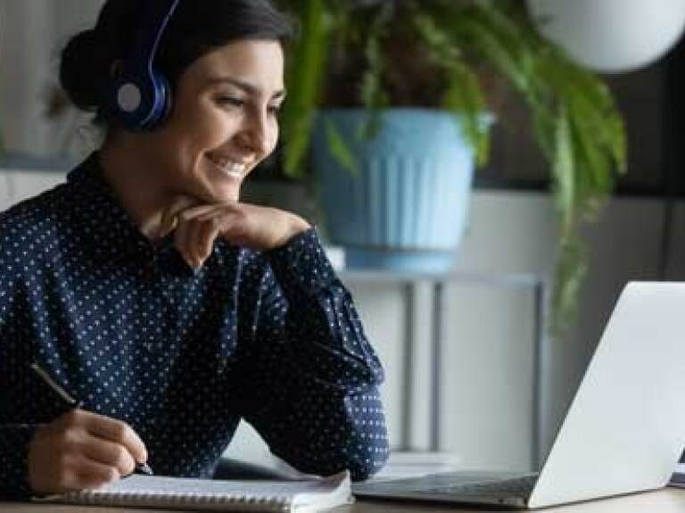 Smiling student wearing headphones and taking notes while seated at a laptop