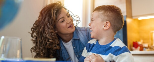 Caregiver and child laughing together in kitchen