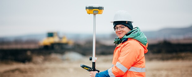GIS technician in the field with surveying gear, hard hat, and reflective jacket