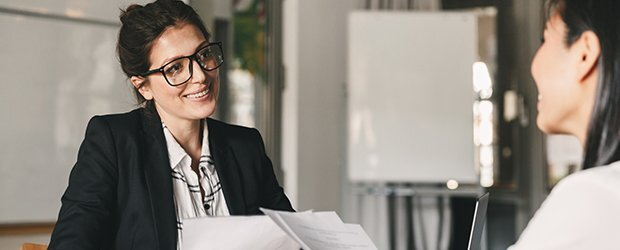 woman-in-glasses-and-black-blazer-smiling-at-woman-holding-papers-in-front-of-white-board