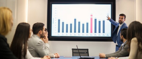 man-in-blue-suit-presenting-blue-and-red-bar-chart-to-audience