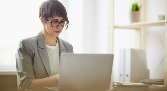 Woman works on a laptop in home office