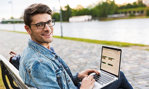 Man-In-Jean-Jacket-With-Glasses-And-Laptop-Sitting-On-Bench-In-Front-Of-Path-And-Water