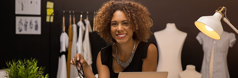 woman-with-computer-in-fashion-office-with-mannequins