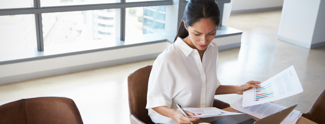 woman-in-white-blouse-sitting-looking-at-papers-on-her-lap