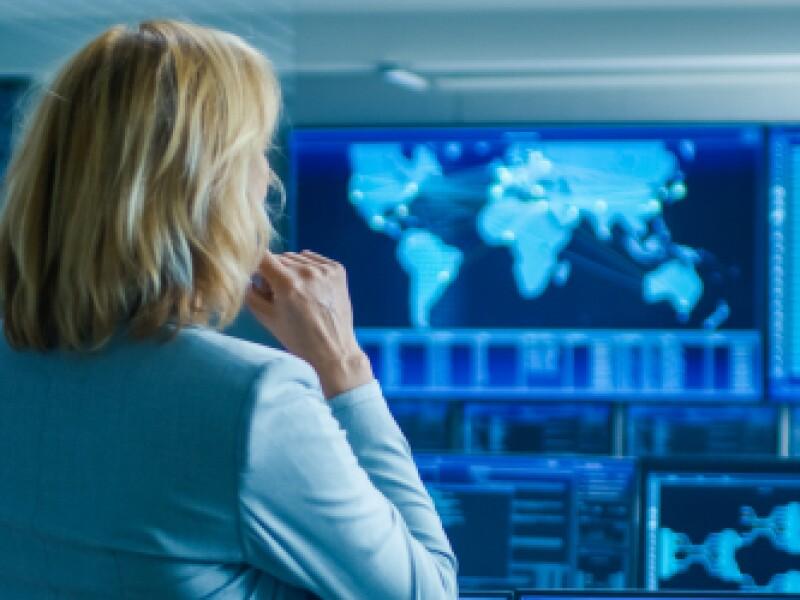 blonde-woman-facing-away-towards-big-screens-with-map