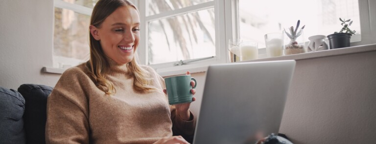Woman sits on her sofa with a coffee cup working on laptop