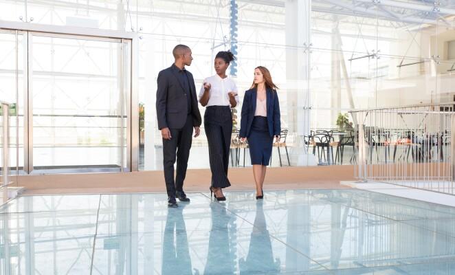 Three professional walk together inside a glass atrium